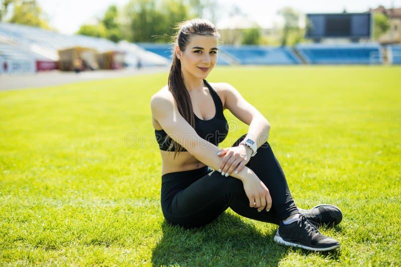Jonge vrouw die na het uitoefenen van zitting op grijs van stadion rusten Geschiktheids mooi meisje De vrouwelijke atleet na werk royalty-vrije stock foto