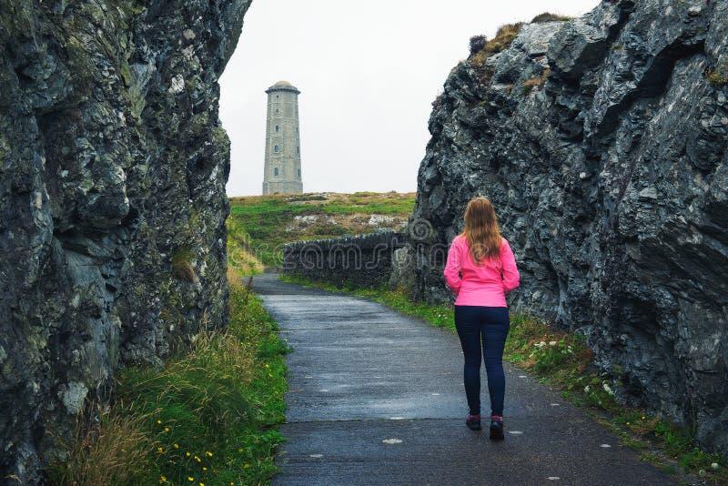 Jonge vrouw die naar de Hoofdvuurtoren van Wicklow in Ierland lopen royalty-vrije stock foto's