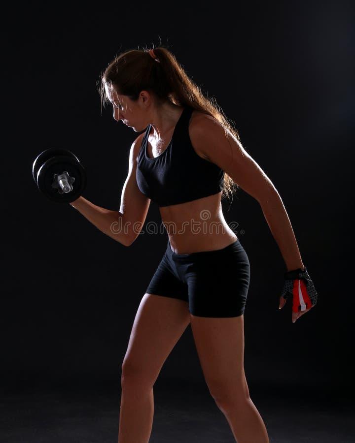 Jonge vrouw die oefening met domoren doen stock foto