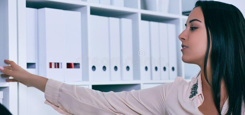 Jonge vrouw die omslag met documenten van plank in archief nemen Heel wat werk in het boekhoudingsbedrijf stock foto
