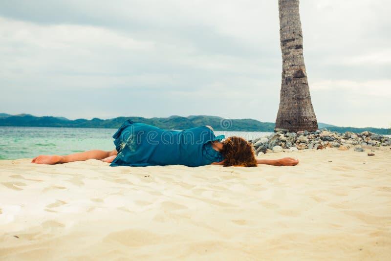 Jonge vrouw die onder palm op strand liggen royalty-vrije stock afbeelding