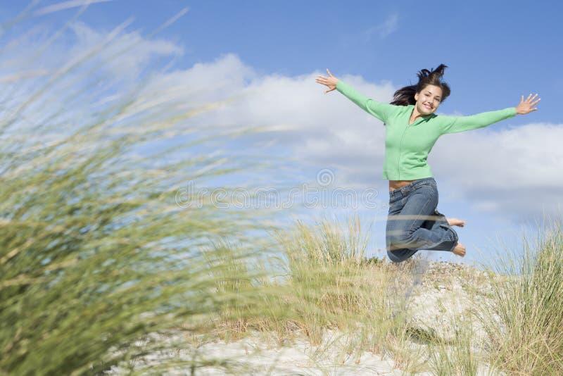 Jonge vrouw die onder zandduinen springt royalty-vrije stock afbeelding