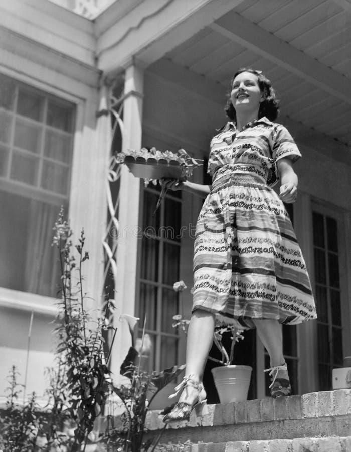 Jonge vrouw die onderaan stappen van haar terras met een plaat in haar handen lopen (Alle afgeschilderde personen leven niet lang stock fotografie