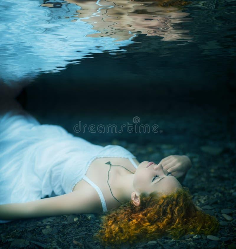 Jonge vrouw die onderwater ligt royalty-vrije stock foto
