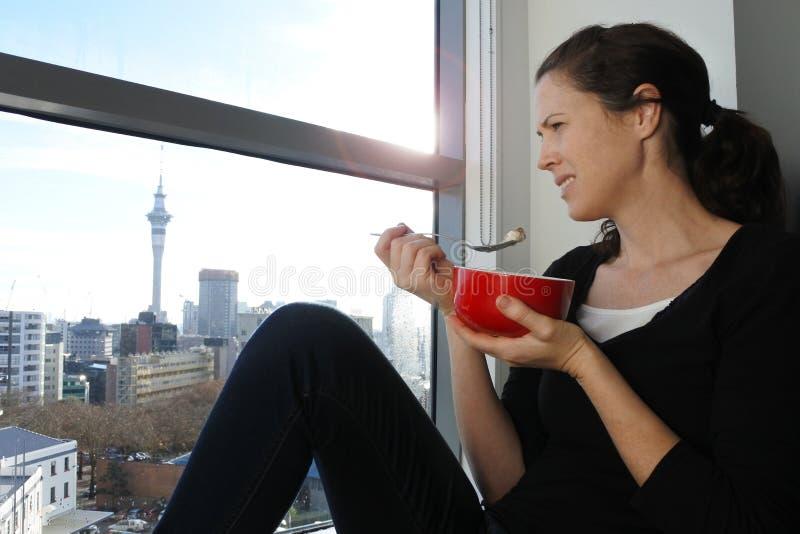 Jonge vrouw die ontbijt eten royalty-vrije stock fotografie