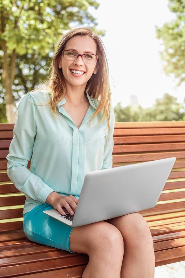 Jonge vrouw die in oogglazen op bank het doorbladeren laptop zitten die camera blij lachen kijken stock afbeelding