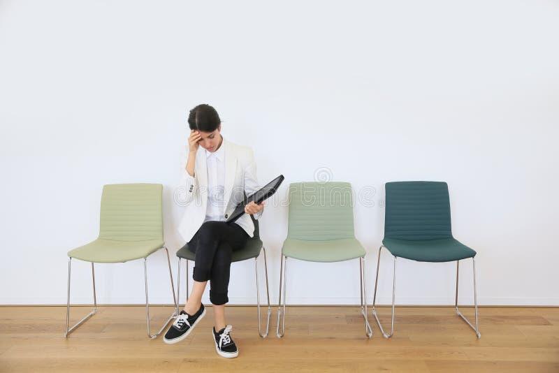 Jonge vrouw die op baangesprek wachten stock afbeelding