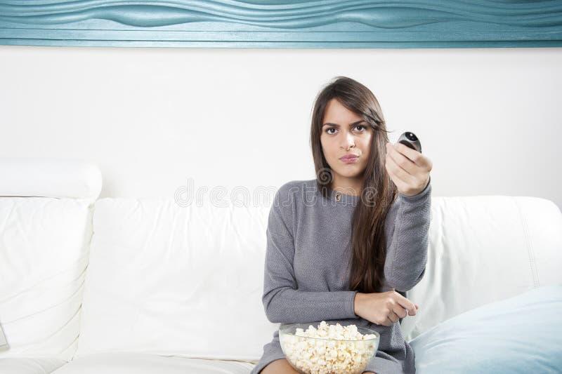 Jonge vrouw die op bank en het letten op film rusten, thuis stock foto's