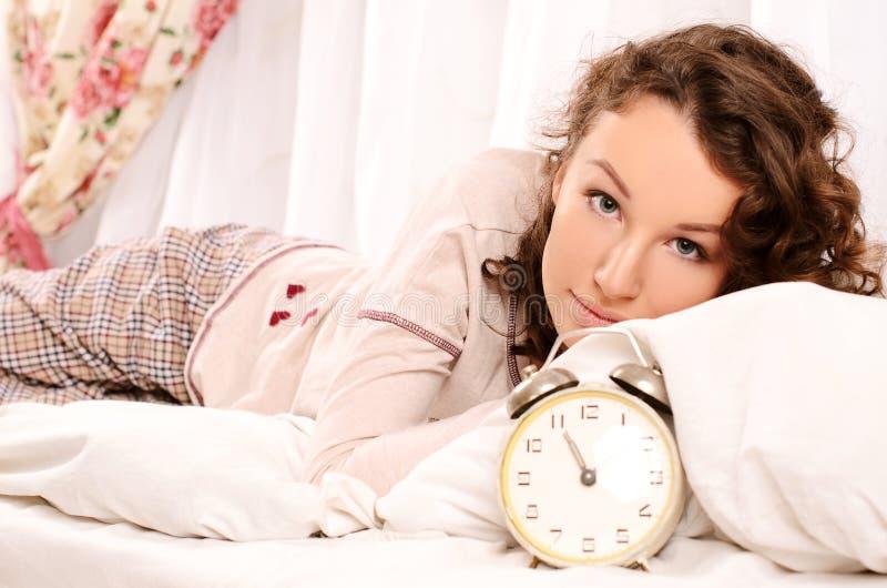 Jonge vrouw die op bed en wekker liggen royalty-vrije stock foto