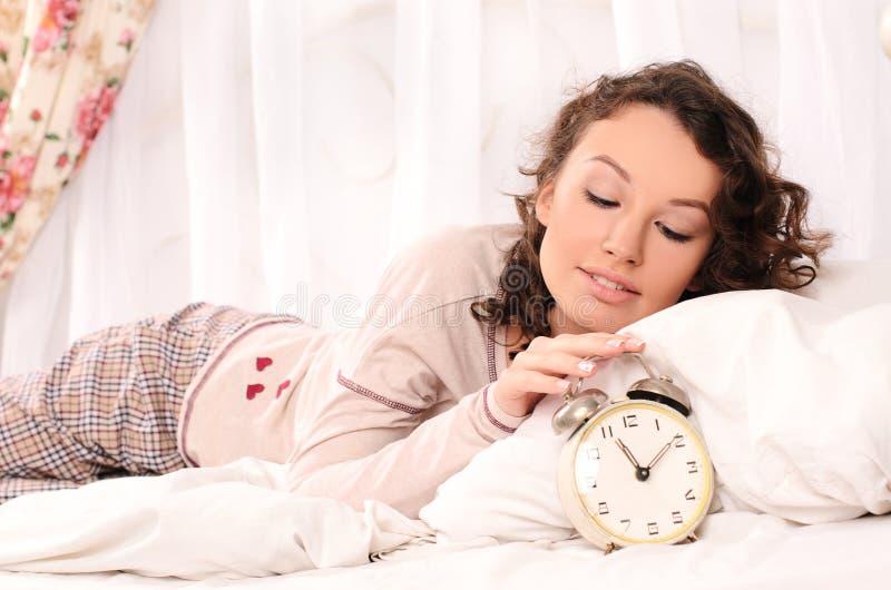 Jonge vrouw die op bed en wekker liggen stock afbeelding