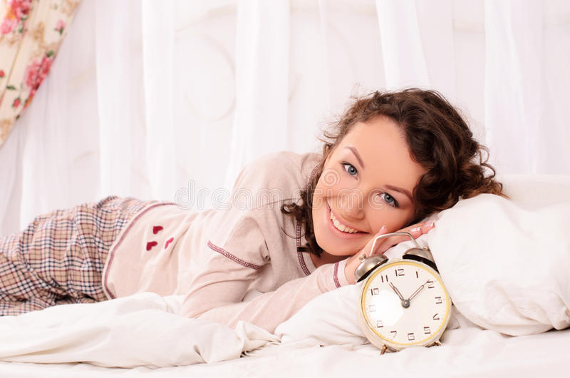 Jonge vrouw die op bed en wekker liggen royalty-vrije stock afbeeldingen
