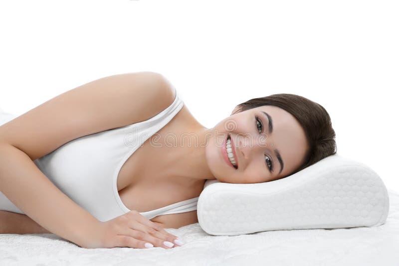 Jonge vrouw die op bed met orthopedisch hoofdkussen liggen stock fotografie