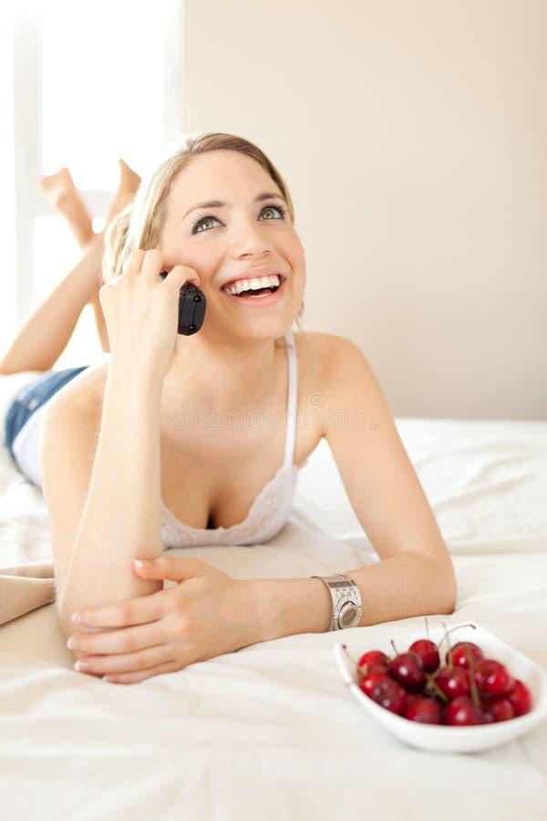Jonge vrouw die op bed spreekt stock afbeelding