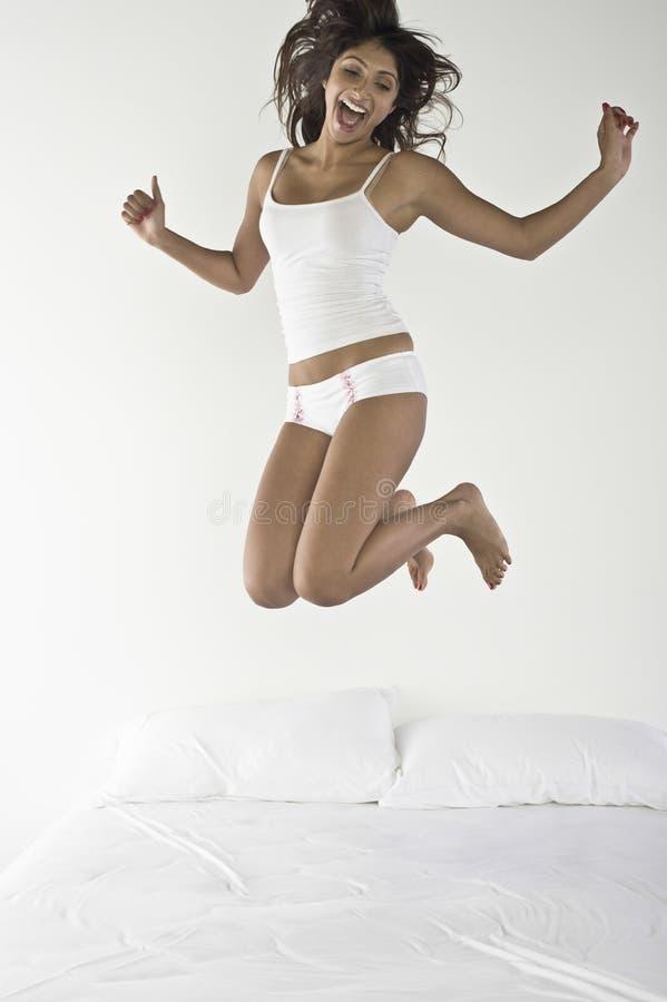 Jonge Vrouw die op Bed springt royalty-vrije stock afbeelding