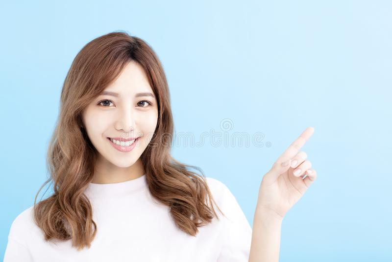 Jonge vrouw die op blauwe achtergrond richten royalty-vrije stock afbeelding