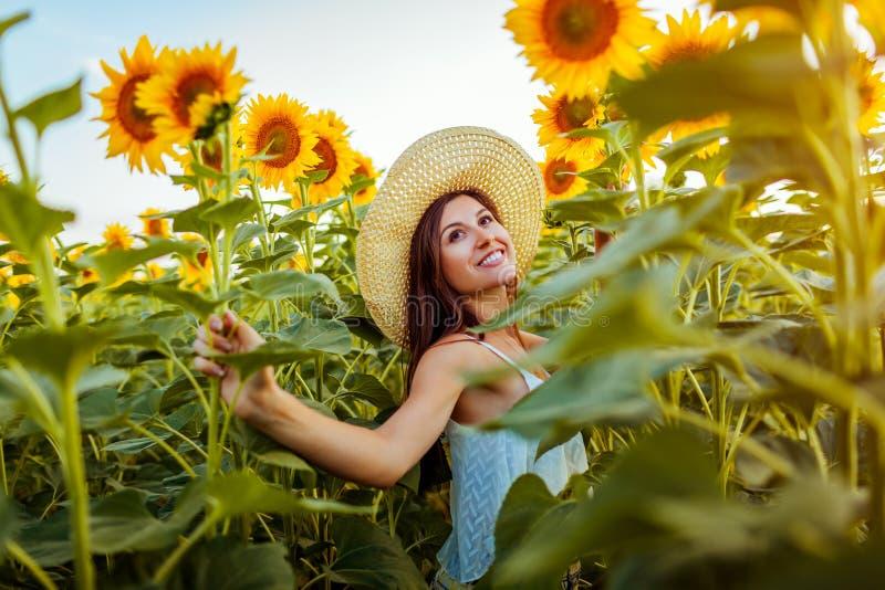 Jonge vrouw die op bloeiend zonnebloemgebied lopen die vrije en het bewonderen aard voelen De vakantie van de zomer royalty-vrije stock foto