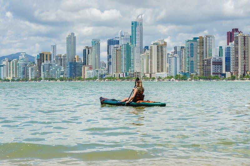 Jonge vrouw die op Braziliaans strand door kayak wandelde Visserijkajak stock foto's