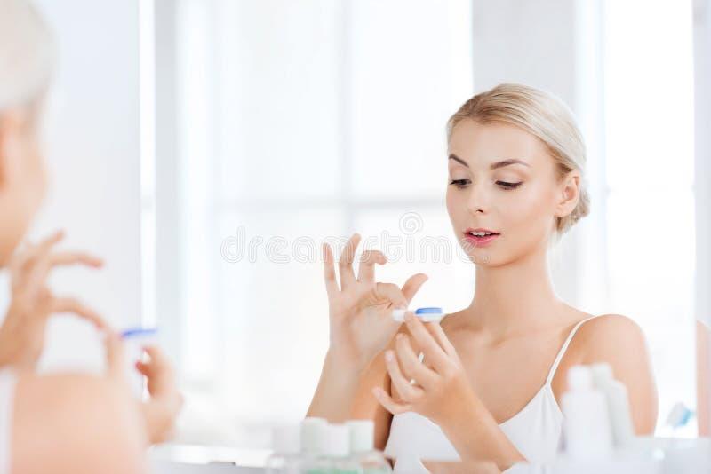 Jonge vrouw die op contactlenzen bij badkamers zetten stock foto