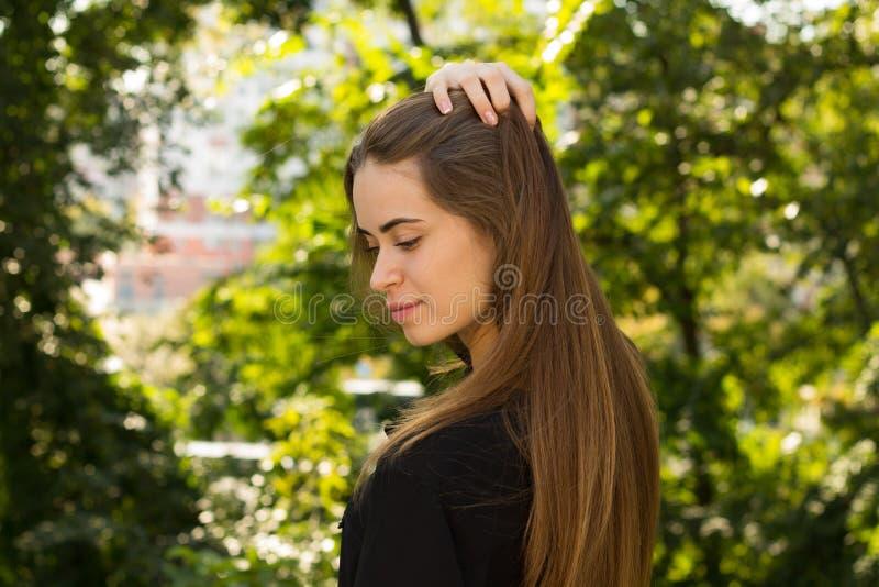Jonge vrouw die op de achtergrond van bomen achteruitgaan royalty-vrije stock foto's