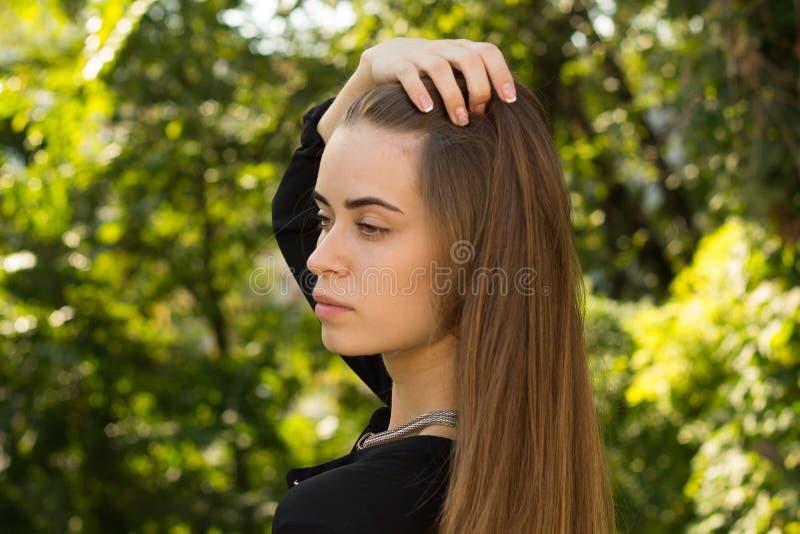 Jonge vrouw die op de achtergrond van bomen achteruitgaan stock afbeeldingen
