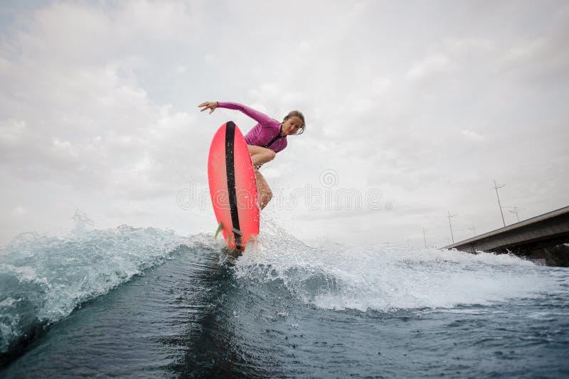 Jonge vrouw die op de blauwe golf tegen de grijze hemel springen royalty-vrije stock foto