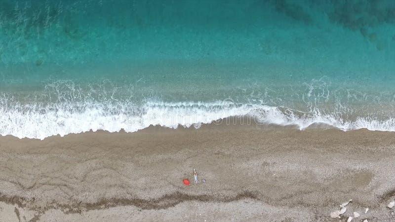 Jonge vrouw die op de rug dichtbij de golven van blauwe overzees liggen lengte Hoogste mening stock afbeelding