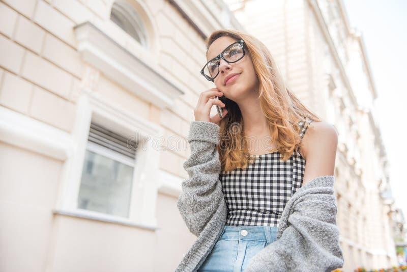 Jonge vrouw die op de telefoon in de straat spreken royalty-vrije stock afbeelding