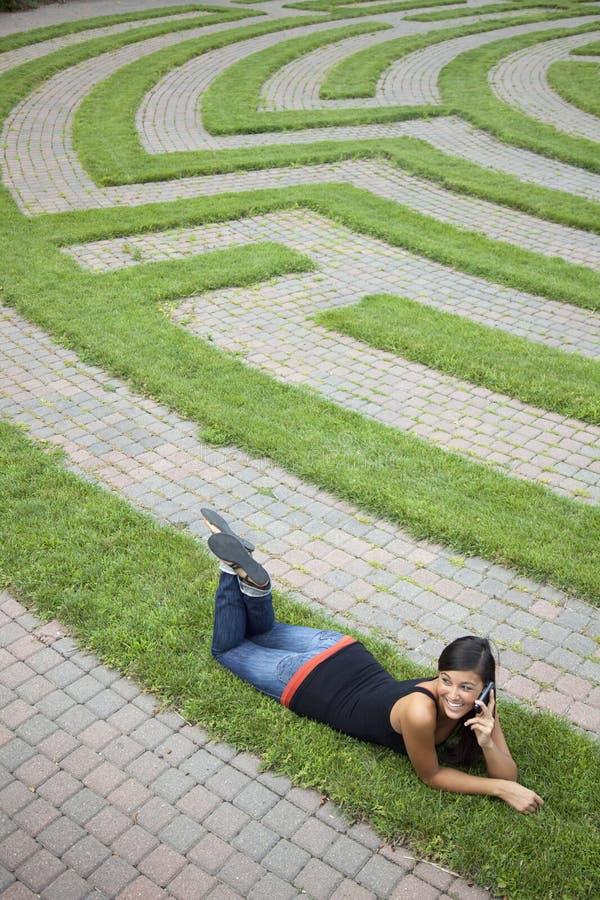 Jonge Vrouw die op de Telefoon in een Labyrint van het Gras spreekt royalty-vrije stock afbeeldingen