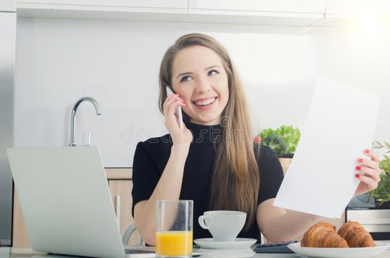 Jonge vrouw die op de telefoon spreken, die in huis werken royalty-vrije stock fotografie
