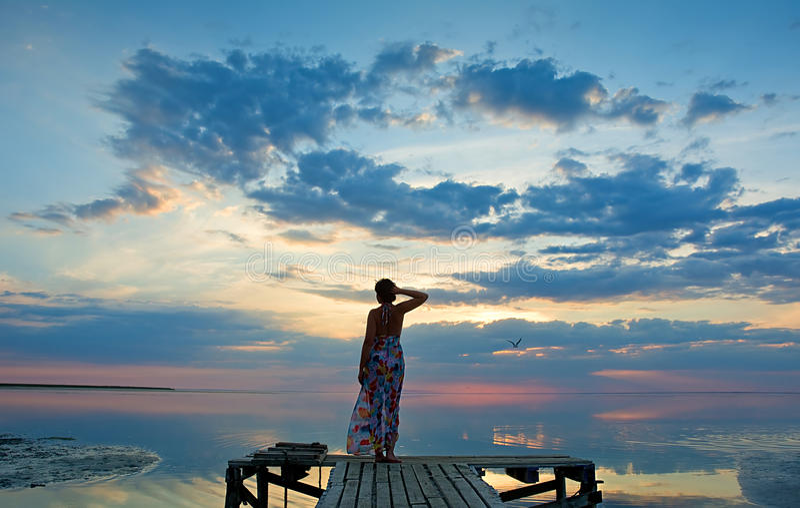 Jonge vrouw die op de zonsondergang op overzeese kust letten royalty-vrije stock foto