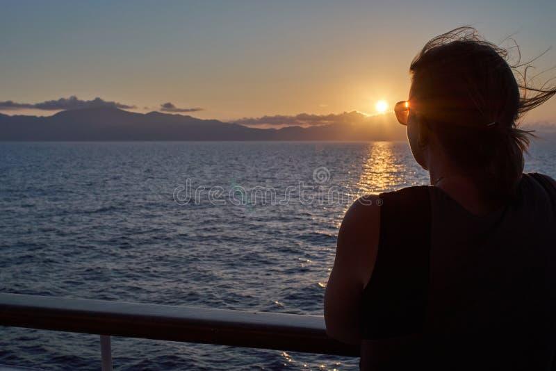 Jonge Vrouw die op de Zonsondergang van een Schip letten royalty-vrije stock foto's
