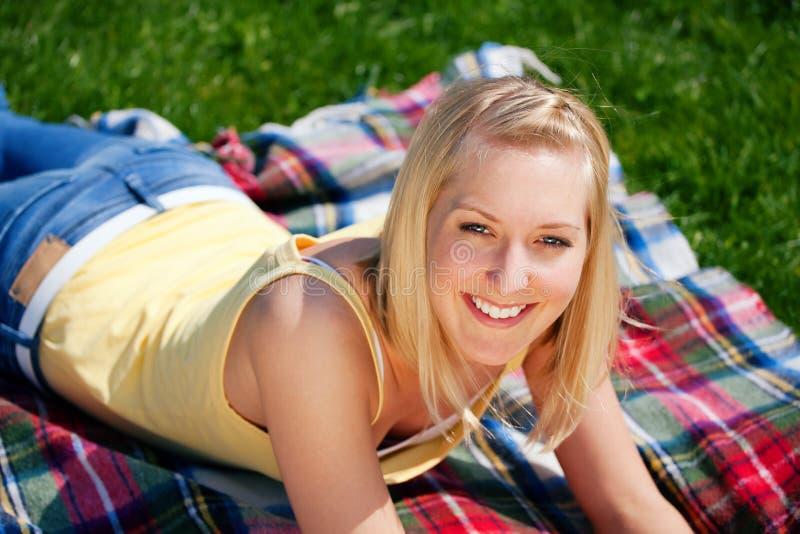 Jonge vrouw die op deken rust stock foto's