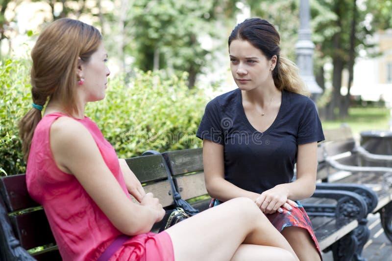 Jonge vrouw die op een bank in het park rusten stock foto's
