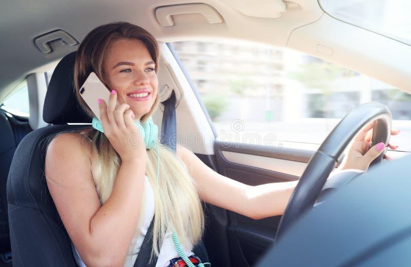 Jonge vrouw die op een cellphone spreken terwijl het drijven van een auto De celtelefoons en het drijven zich mengen niet goed vo stock afbeelding