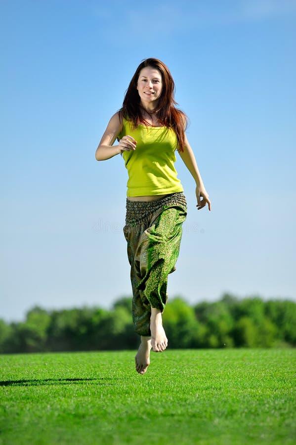 Jonge vrouw die op een groene weide lopen stock fotografie
