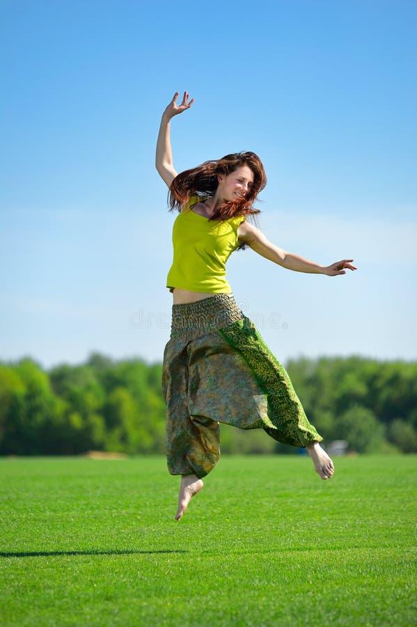 Jonge vrouw die op een groene weide springen stock foto