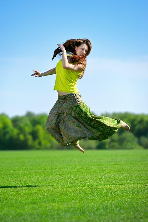 Jonge vrouw die op een groene weide springen stock afbeeldingen
