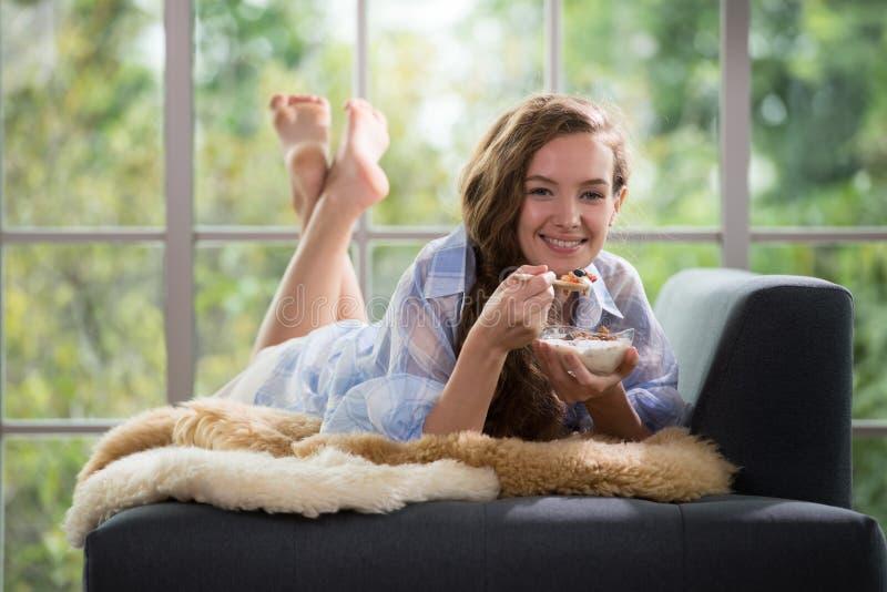 Jonge vrouw die op een laag liggen die een kom yoghurt houden royalty-vrije stock afbeeldingen
