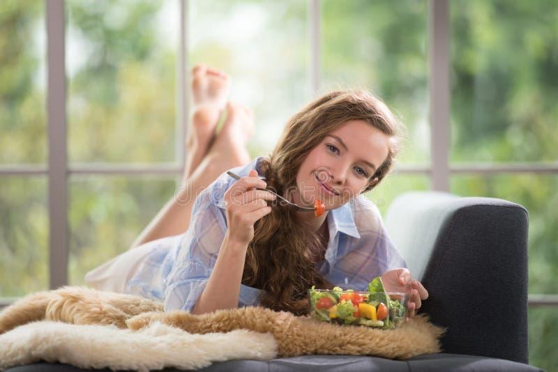 Jonge vrouw die op een laag liggen die een saladekom houden stock fotografie