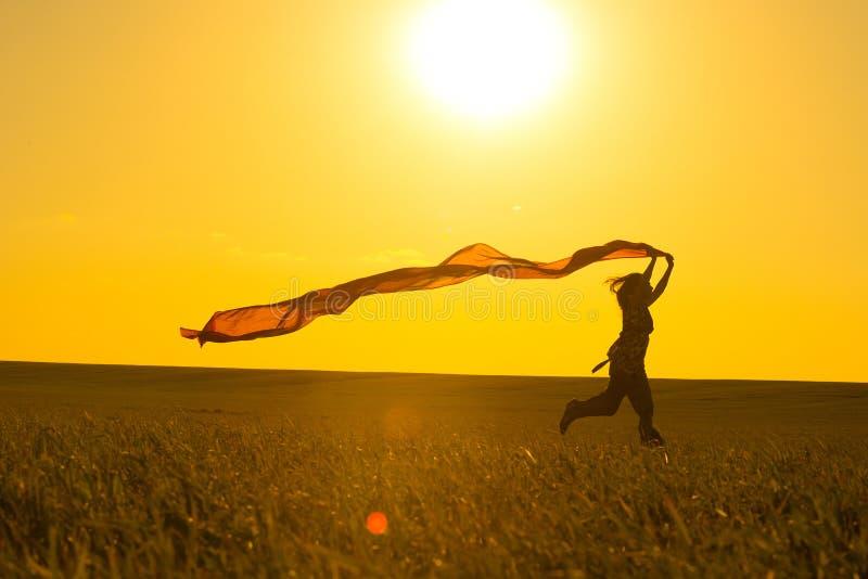 Jonge vrouw die op een landelijke weg bij zonsondergang binnen lopen royalty-vrije stock afbeelding