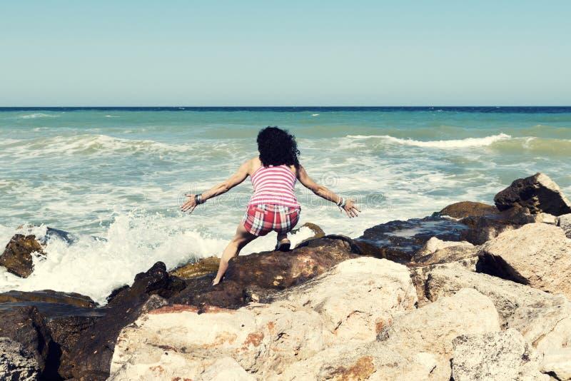 Jonge vrouw die op een overzees strand hurken die van het mooie zonnige weer genieten royalty-vrije stock fotografie