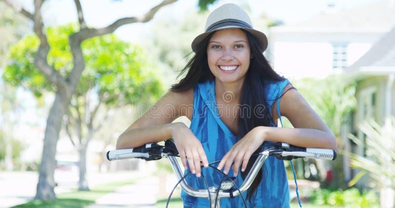 Jonge vrouw die op fiets glimlachen stock foto