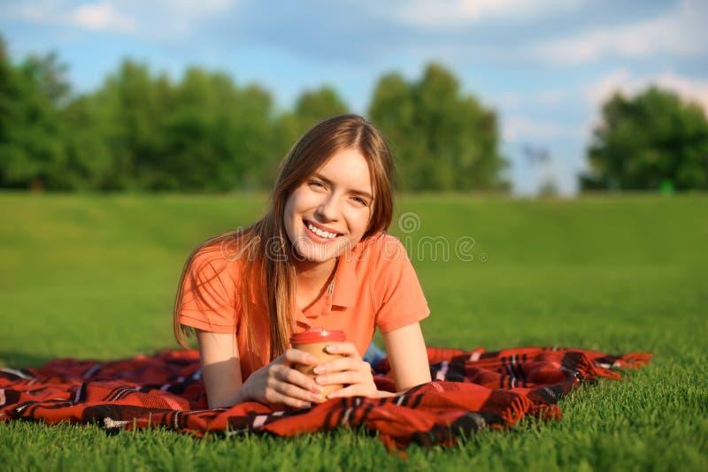 Jonge vrouw die op groen gras in openlucht liggen royalty-vrije stock afbeelding