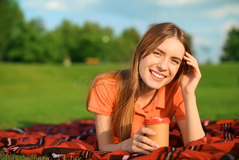 Jonge vrouw die op groen gras in openlucht liggen royalty-vrije stock fotografie