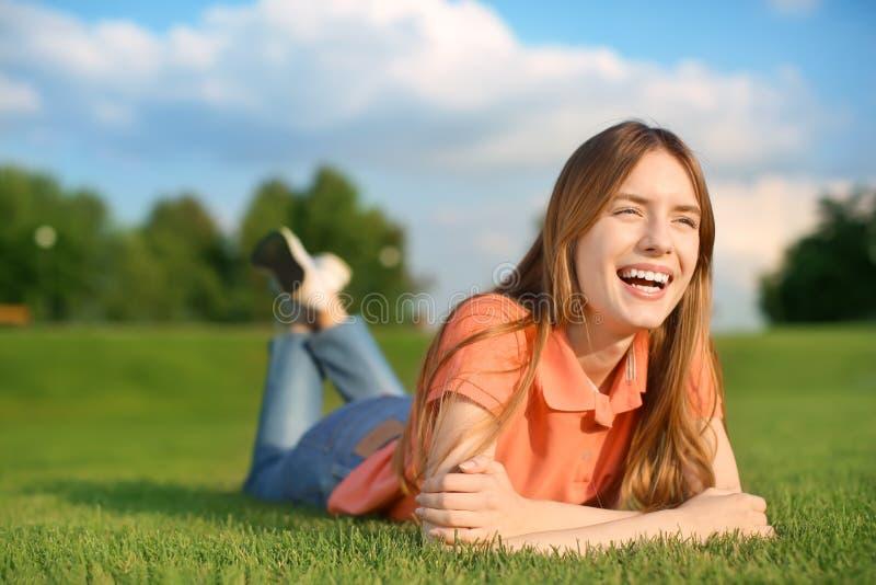 Jonge vrouw die op groen gras in openlucht liggen royalty-vrije stock foto