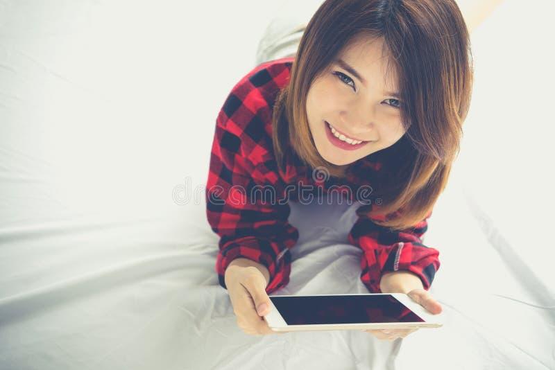 Jonge vrouw die op haar bed liggen die tabletpc met behulp van die Internet surfen B royalty-vrije stock afbeeldingen