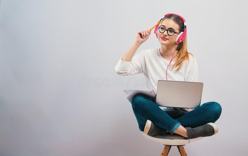 Jonge vrouw die op haar laptop computer bestuderen stock foto's