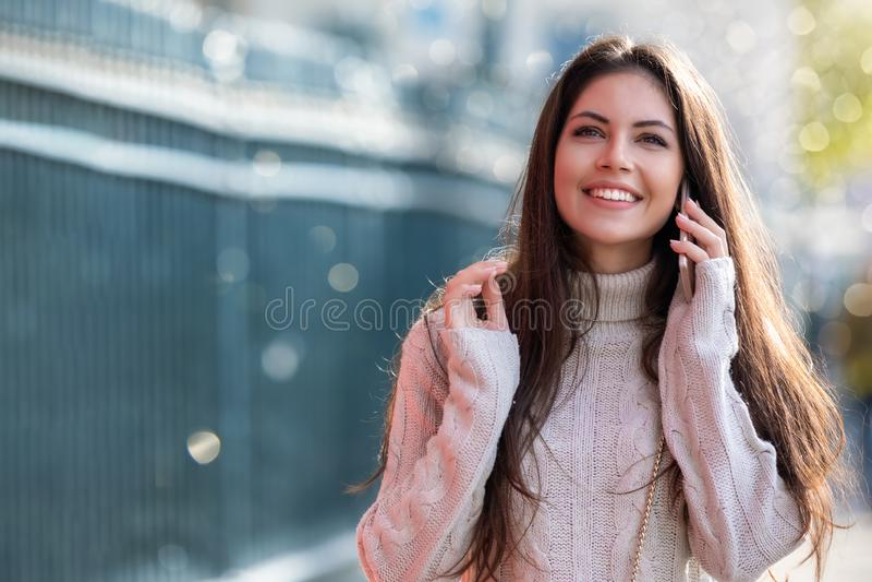 Jonge vrouw die op haar mobiele telefoon in de stad spreken royalty-vrije stock afbeelding