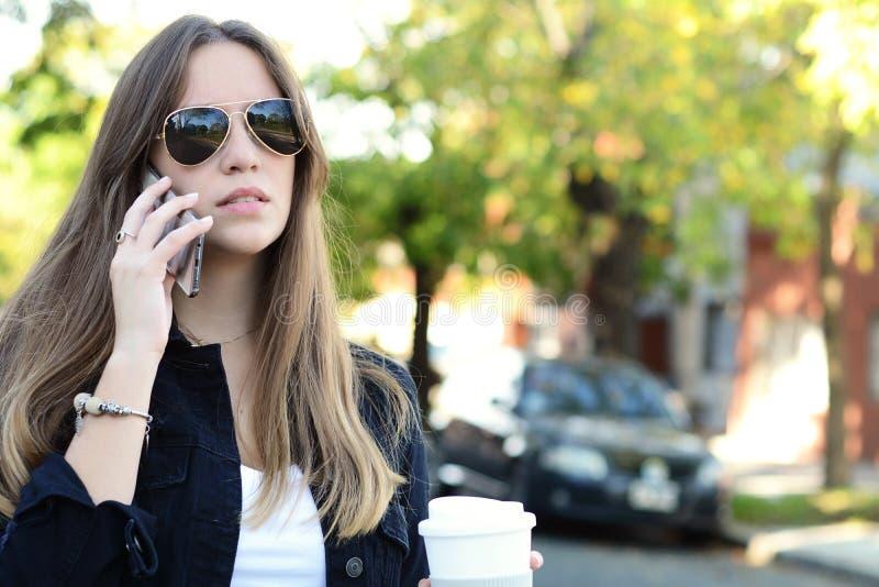 Jonge vrouw die op haar mobiele telefoon met ithkoffie spreken stock afbeeldingen
