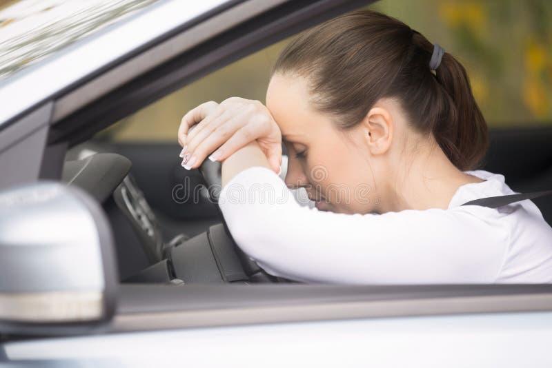 Jonge vrouw die op haar telefoon spreken die een auto drijven stock afbeeldingen